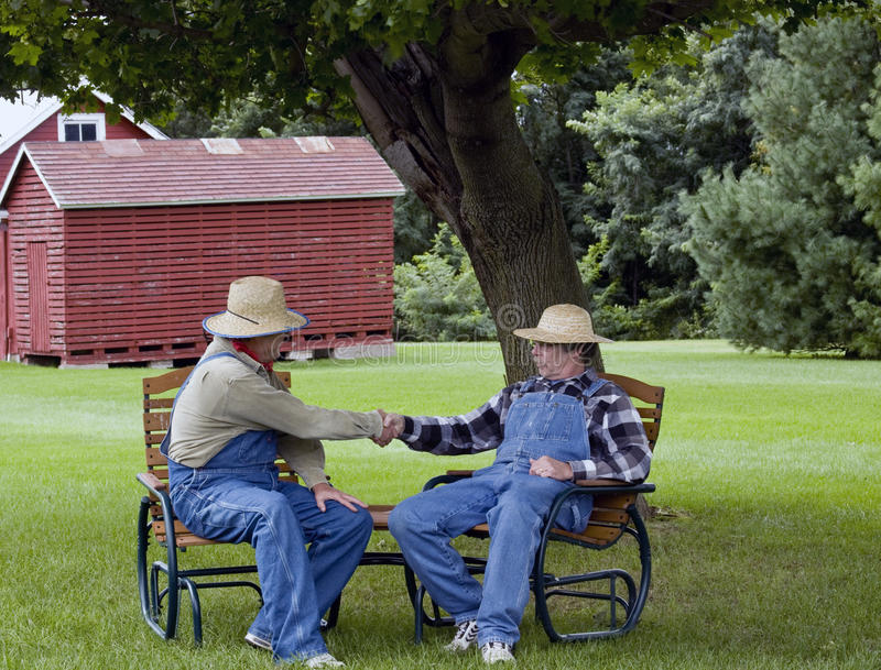 Farmers handshake. Two farmers in bib overalls shaking hands sitting in lawn chairs royalty free stock images