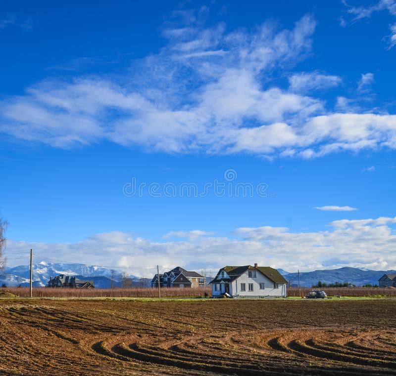 Farmers` houses on the field on winter season in British Columbia royalty free stock image