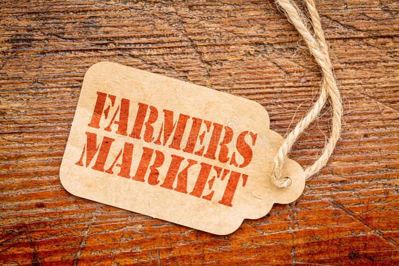 Farmers market - price tag sign. Farmers market - red stencil text on a paper price tag against rustic wood royalty free stock image