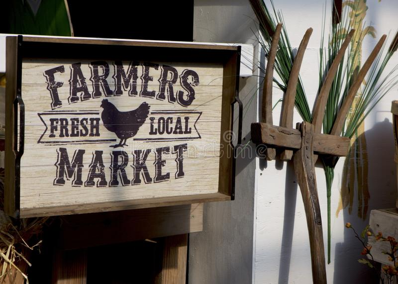 Country Farmers Market Sign. Farmers Market Sign flanked by a wooden pitchfork.  Vertical.  Country.  Colors: Brown, Beige, Gray stock images