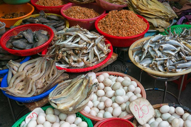 Farmers market stall selling eggs and cured seafood with dry fish. Vietnam stock photo