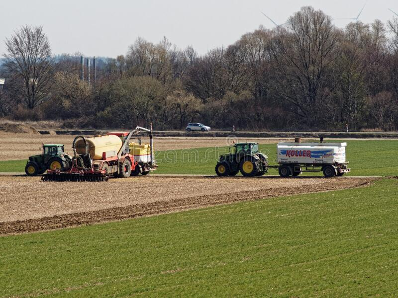 Farmers with tractors on field sowing for food supply stock photo