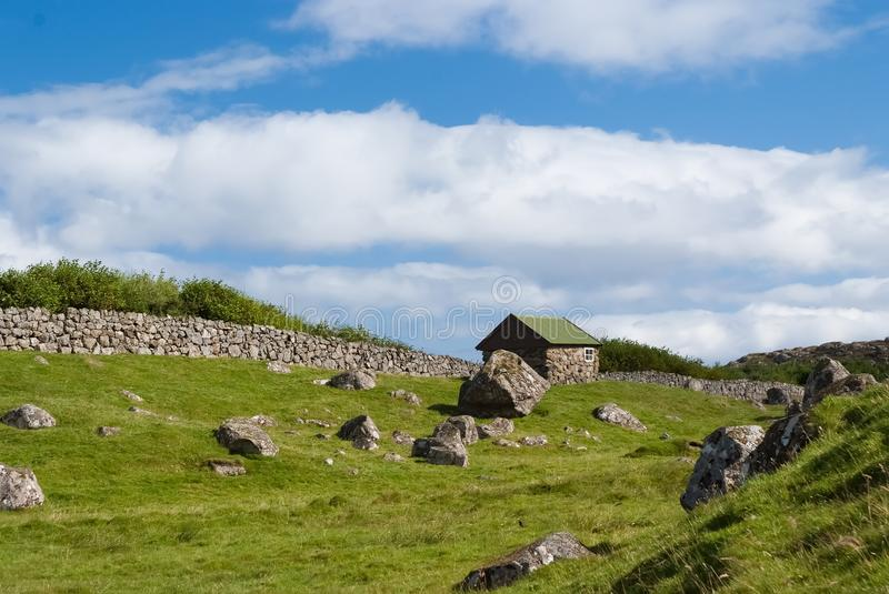 Farmhouse in Torshavn, Denmark. Old stone house in farm yard on cloudy blue sky. Typical rural architecture. Nature and. Environment. Beautiful landscape view royalty free stock photo