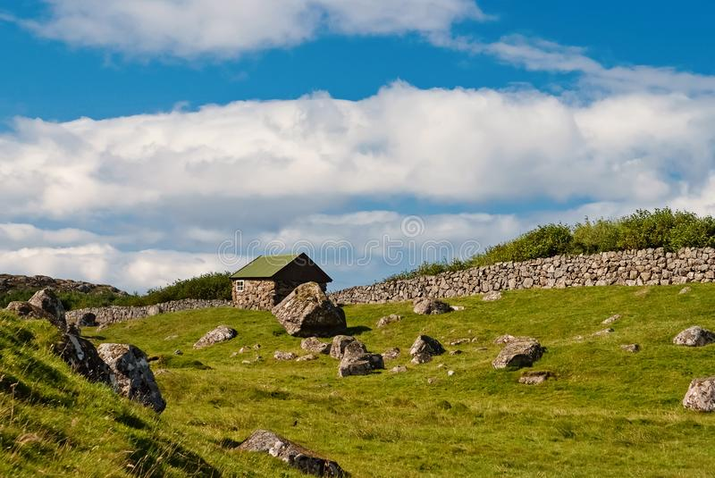 Farmhouse in Torshavn, Denmark. Old stone house in farm yard on cloudy blue sky. Typical rural architecture. Nature and. Environment. Beautiful landscape view royalty free stock images