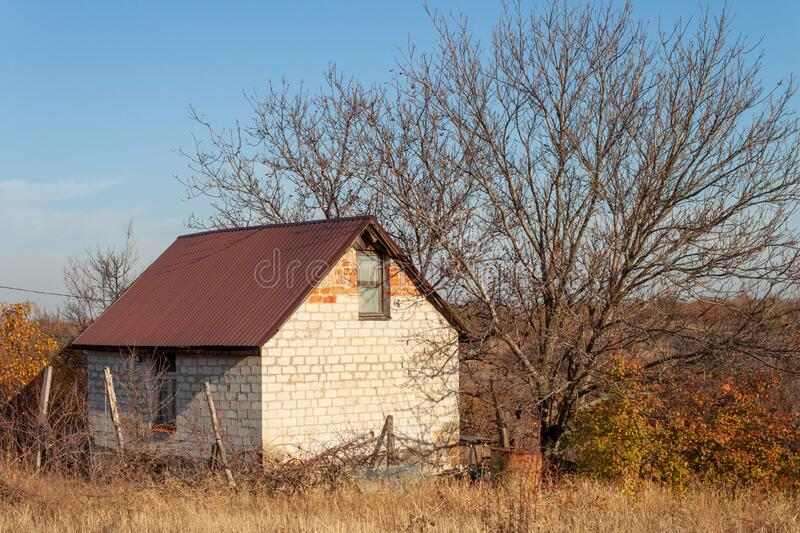 Farmhouse in the village on an autumn sunny day at sunset royalty free stock images