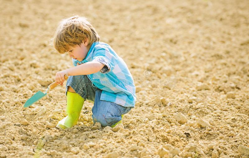 Farming and agriculture. small kid planting a flower. ecology life. Cultivation concept. earth day. new life. summer. Farm. happy child gardener. botanic worker stock image