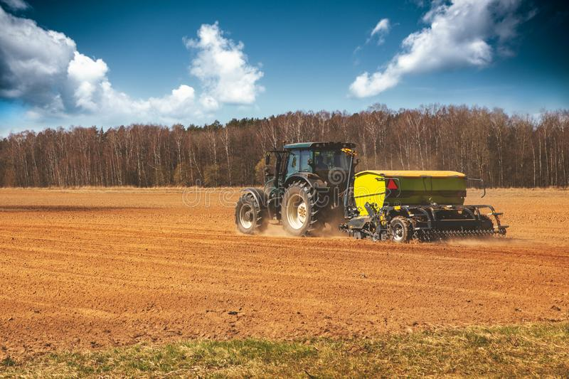 Farming - farmer with tractor on the field seeding sowing crops royalty free stock photography
