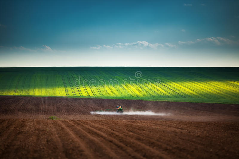 Farming tractor plowing and spraying on field royalty free stock photos