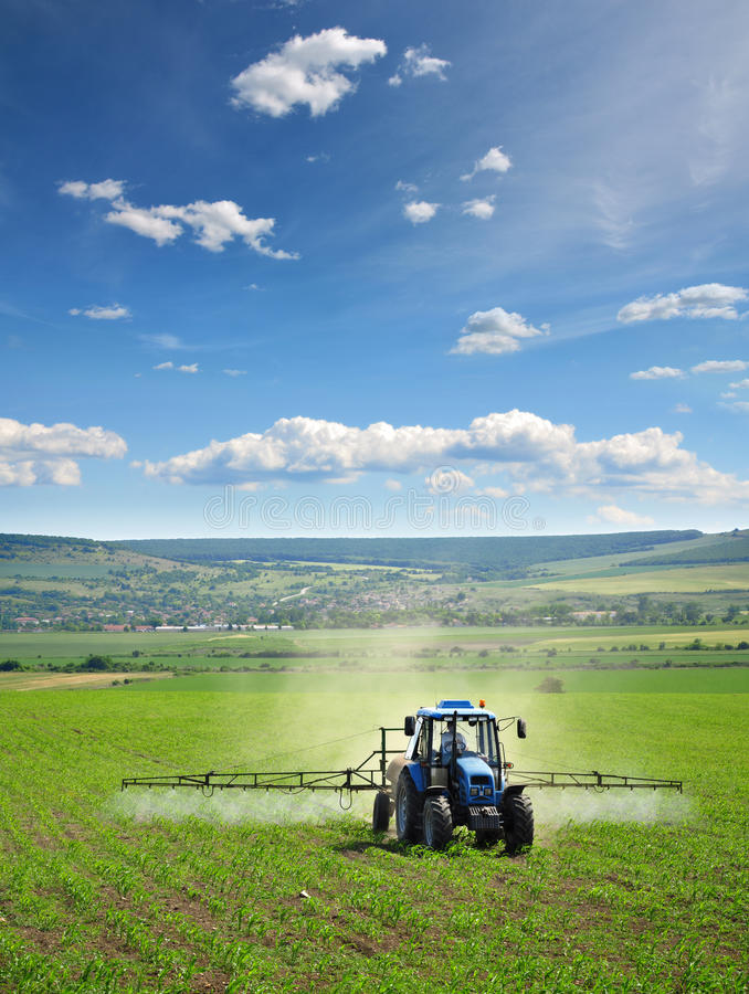 Farming tractor plowing and spraying on field royalty free stock images