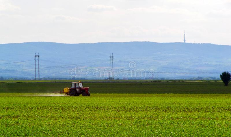 Farming tractor plowing and spraying on field royalty free stock image