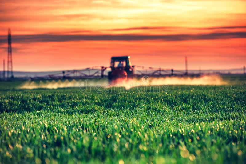 Farming tractor plowing and spraying on field by the sunset royalty free stock photography