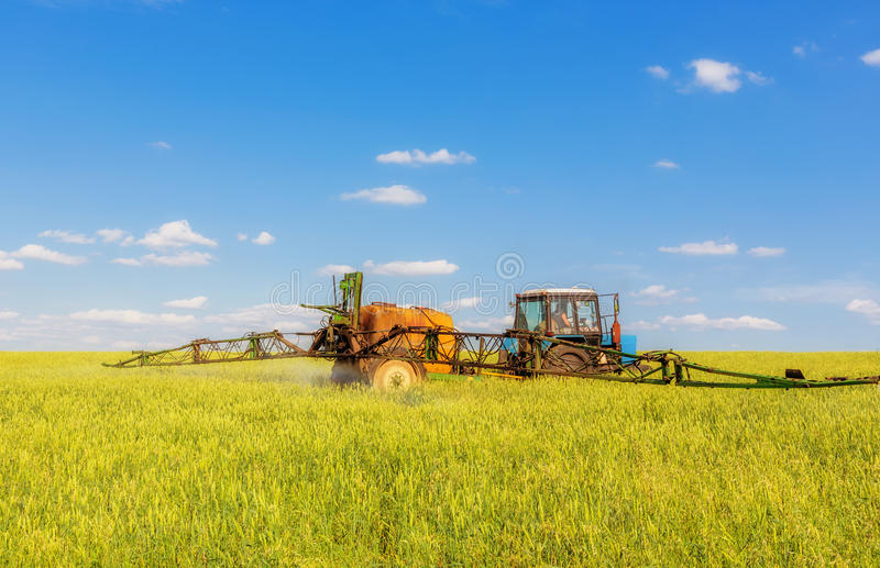 Farming tractor spraying green field. Beneath blue sky with white clouds stock photos