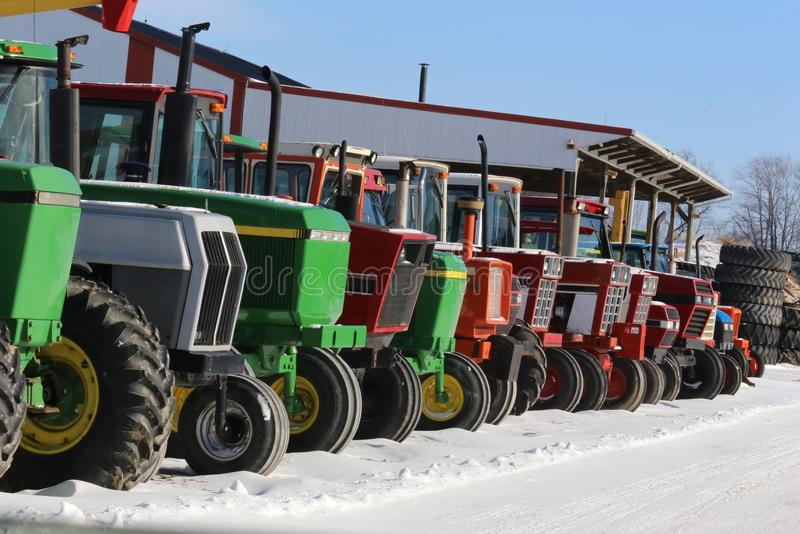 Farming tractors. Various models and colors of farming tractors are lined up for display royalty free stock photos