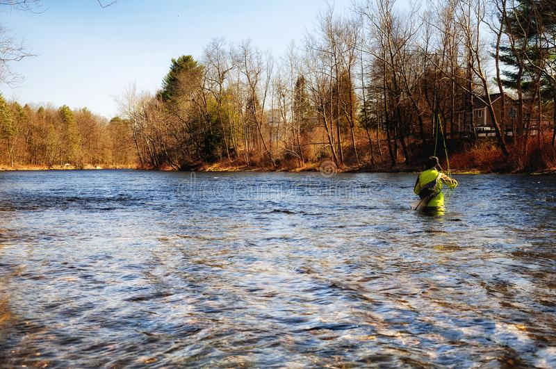 Farmington River Pleasant Valley Connecticut. A fly fisherman standing in the Farmington River in Pleasant Valley Connecticut on a sunny spring afternoon royalty free stock photography