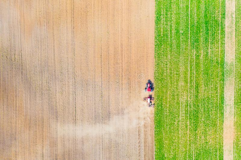 Farmland aerial texture. Tractor ploughing field in dry season royalty free stock image
