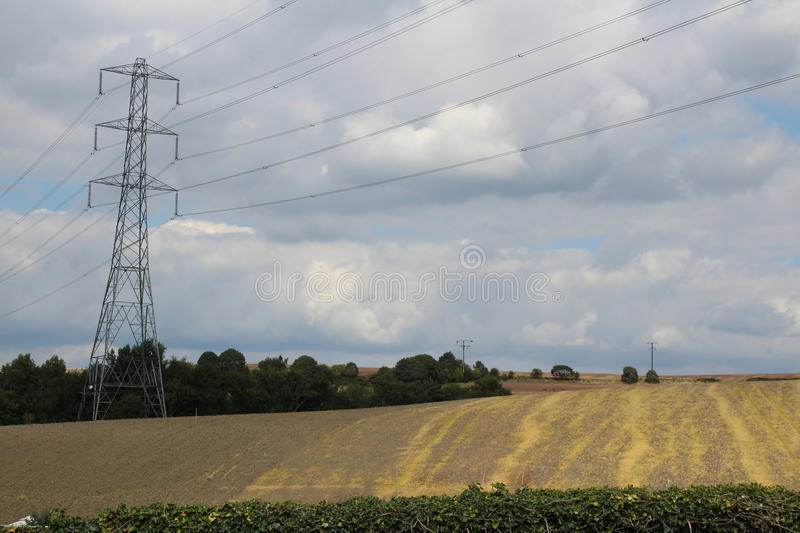 Farmland of harvested crops and pylon. With woods stock image