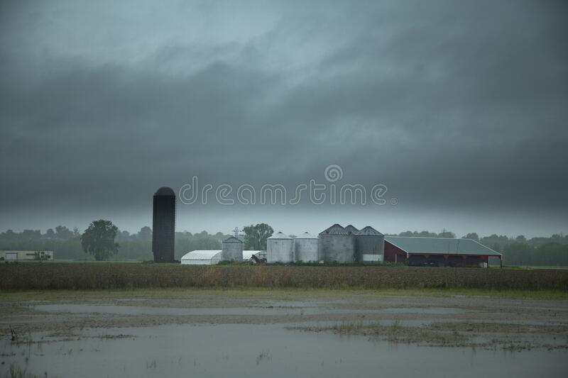Farmland with industrial buildings under the dark cloudy dramatic sky. A farmland with industrial buildings under the dark cloudy dramatic sky royalty free stock photo