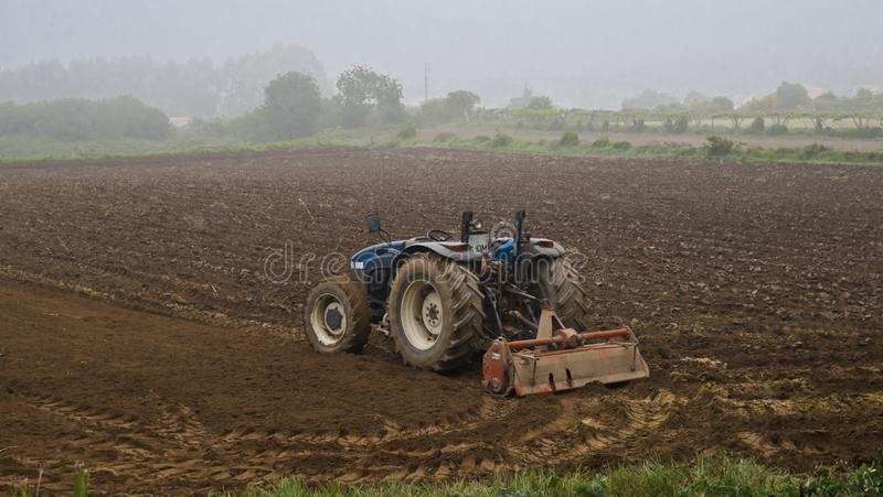 Farmland roadster. Abandoned blue farmland tractor parked at the edge of a fertile field early moring mist. absent driver rual countryside places time seasons royalty free stock photos