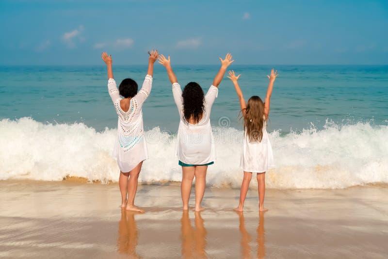 Farmodern, dottern och sondottern lyftte deras händer upp på en solig dag o arkivbilder