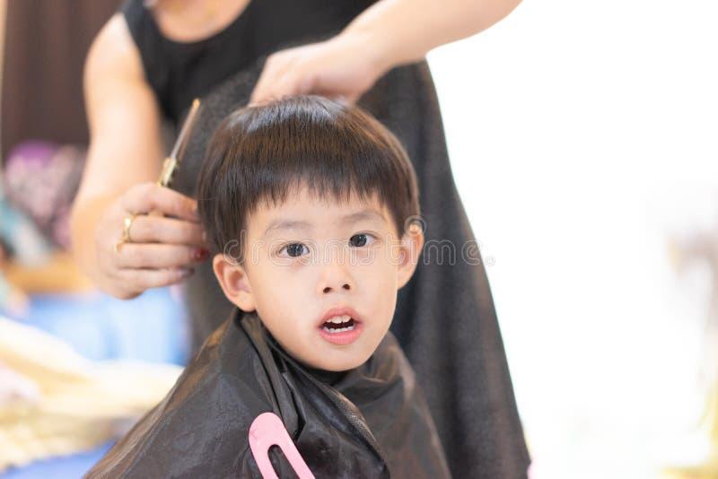 Farmodern klipper hår av hennes sonson hemma fotografering för bildbyråer
