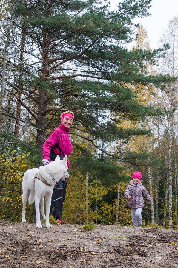 Farmodern med hennes sondotter och en hund går parkerar in royaltyfria foton