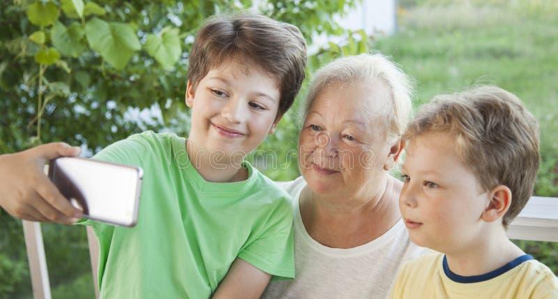 Farmodern och barnbarn gör Selfie i sommarträdgården Fa arkivfoton