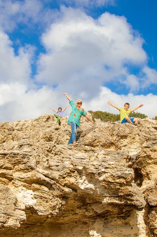 Farmodern och barnbarn vaggar klättring royaltyfria foton