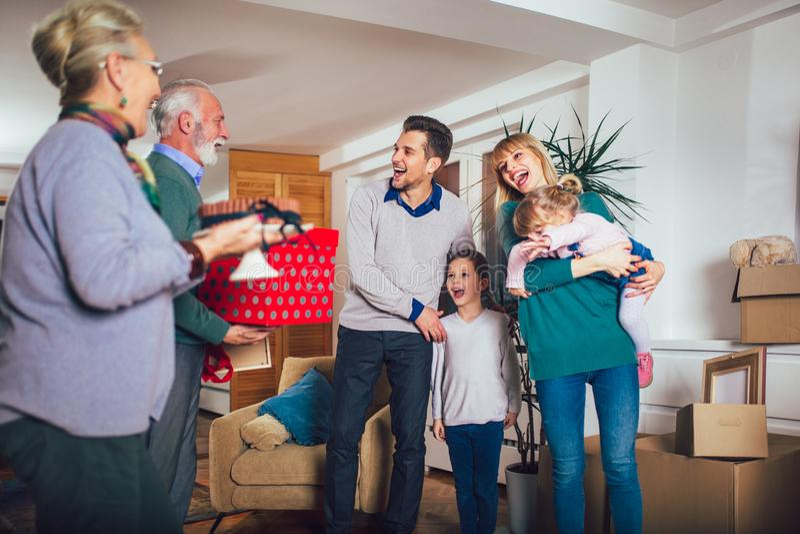 Farmodern och farfadern kommer med en gåva för att flytta sig in i en ny lägenhet till barn royaltyfria foton