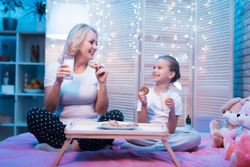 Farmodern och sondottern äter kakor med mjölkar på natten hemma arkivbilder