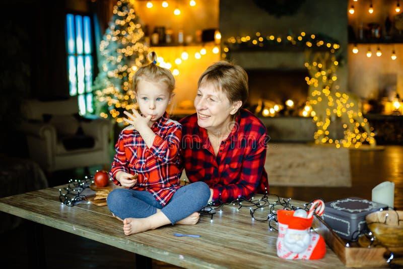 Farmodern och sondottern möter tillsammans julmorgon i ett jaga hus som dekoreras med girlander arkivbild