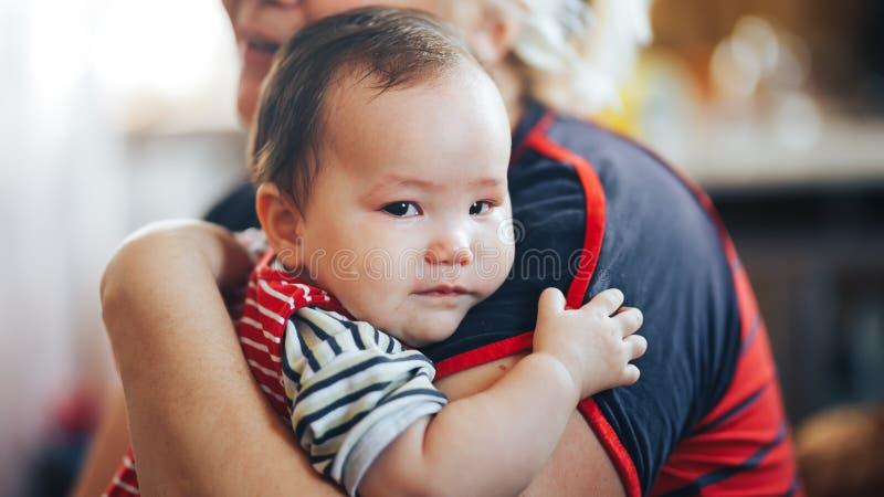 Farmodern som vaggar gråta spädbarnet, behandla som ett barn flickan som ser kameran fotografering för bildbyråer