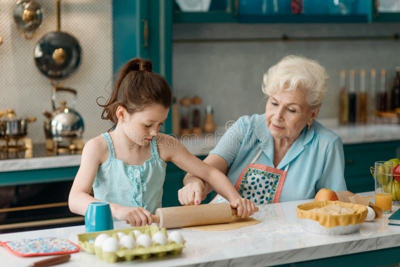Farmodern undervisar sondottern att baka arkivfoton