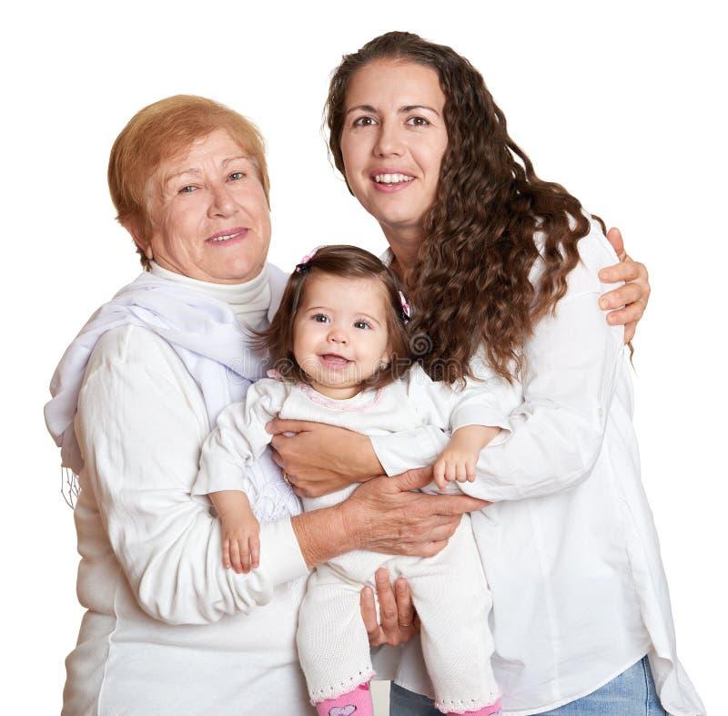 Farmor, dotter och sondotter på den vita ståenden, lyckligt familjbegrepp royaltyfri foto