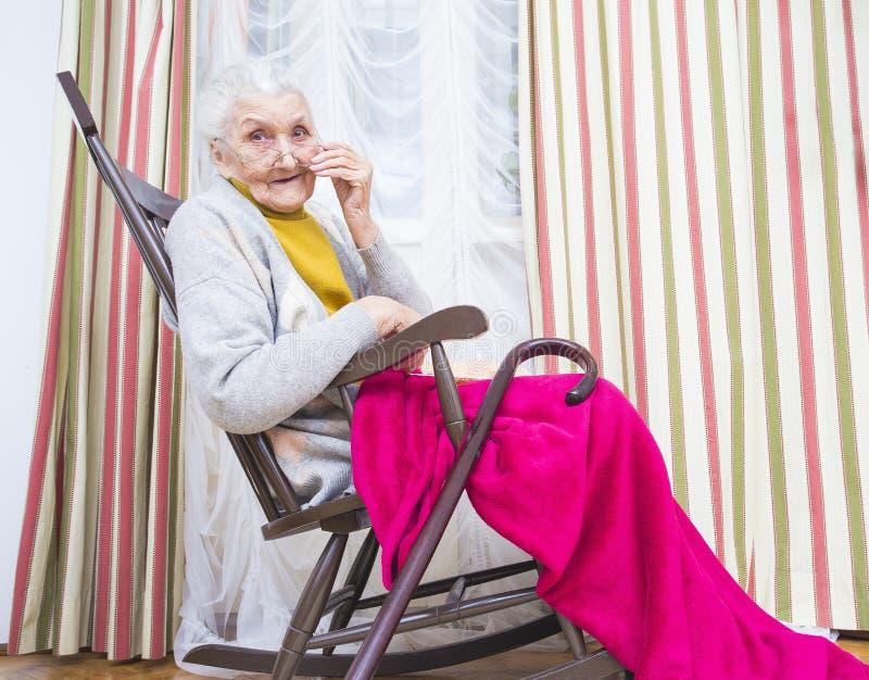 Farmor i en stol arkivfoto