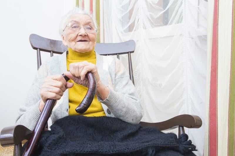 Farmor i le för stol royaltyfri bild