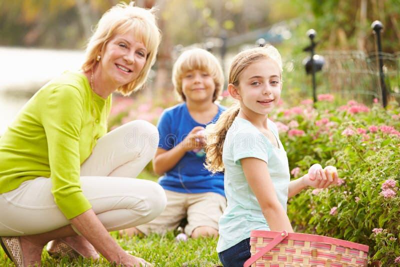 Farmor med barnbarn på påskägget Hunt In Garden royaltyfri fotografi