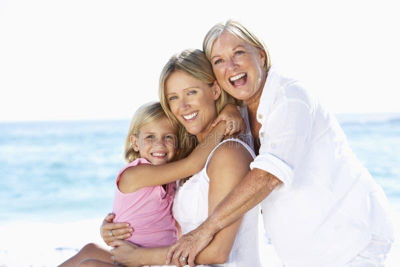 Farmor med dottern och sondottern som omfamnar på strandferie royaltyfria bilder