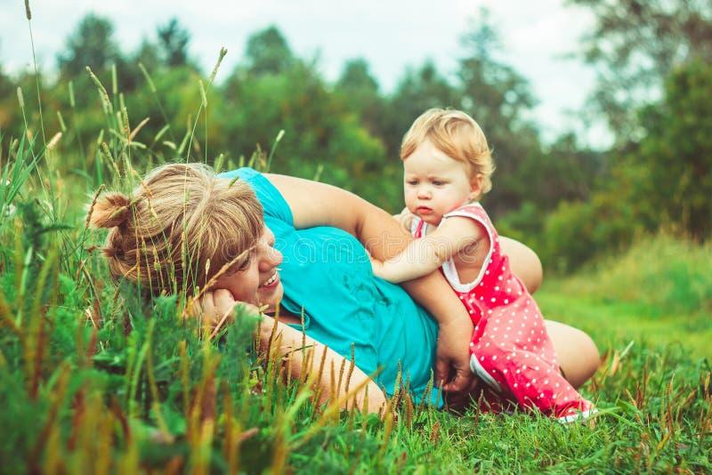 Farmor med sondottern på gräset royaltyfria foton