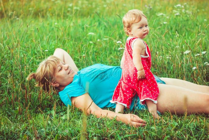 Farmor med sondottern på gräset arkivbild
