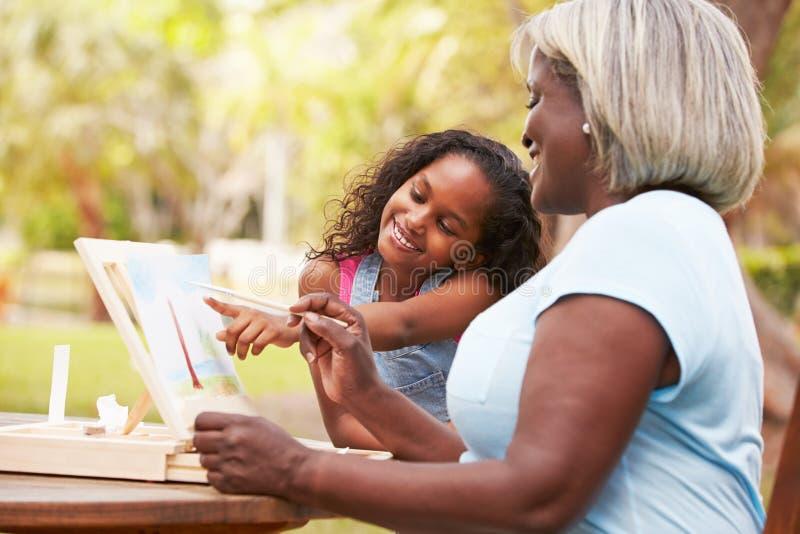 Farmor med sondottern som målar utomhus landskap arkivbild