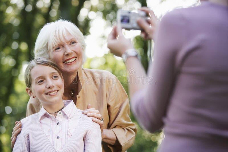 Farmor med sondottern som poserar för fotografi arkivbild