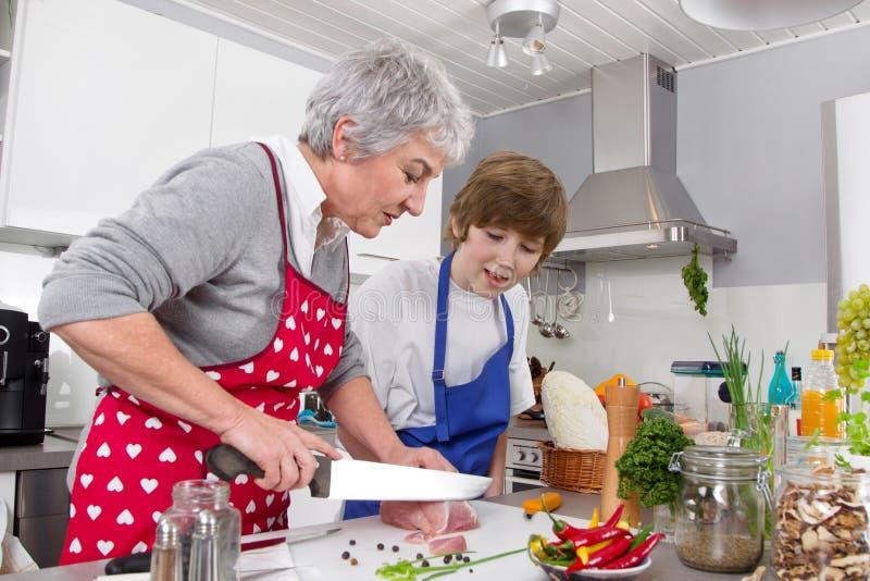 Farmor med sonsonen i köket som förbereder stekkött arkivbild