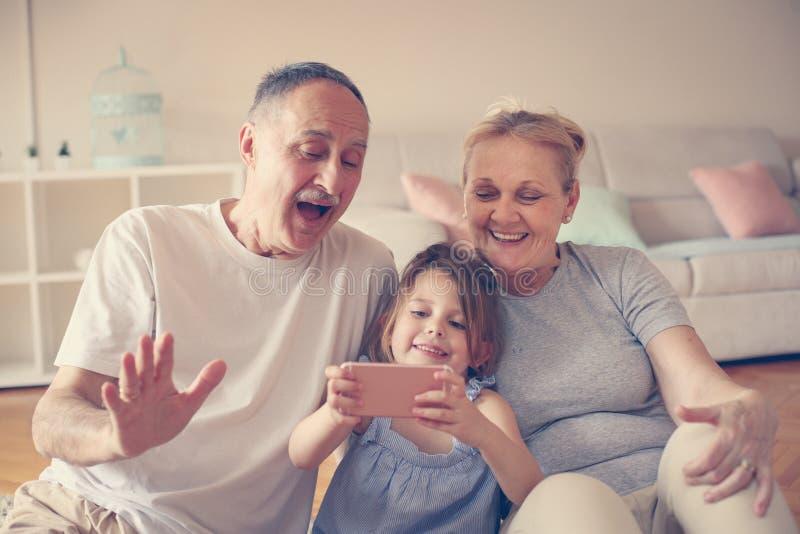 Farmor och farfar med deras använda för sondotter som är smart royaltyfria bilder
