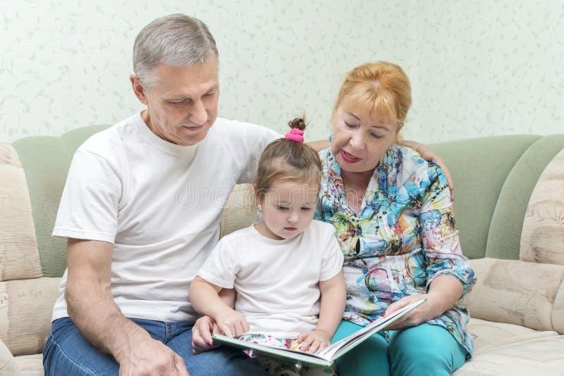 Farmor och farfar med sondottern på soffan royaltyfria foton