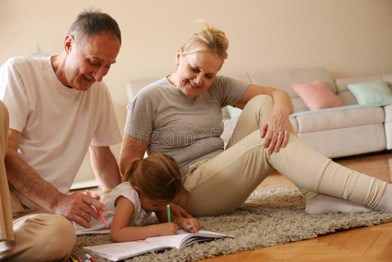 Farmor och farfar som undervisar deras sondotter till writen royaltyfria bilder
