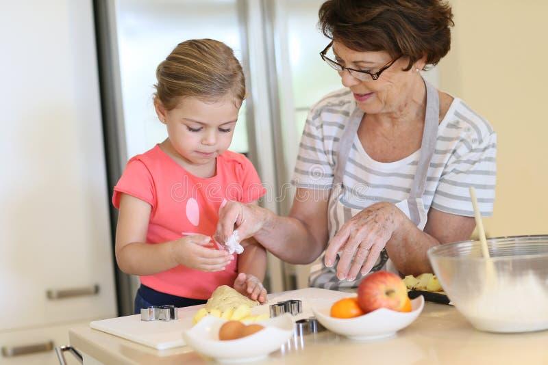 Farmor och hennes sondotter som tillsammans lagar mat arkivfoto