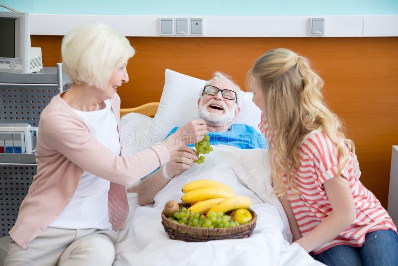 Farmor och sondotter som besöker patienten royaltyfri fotografi