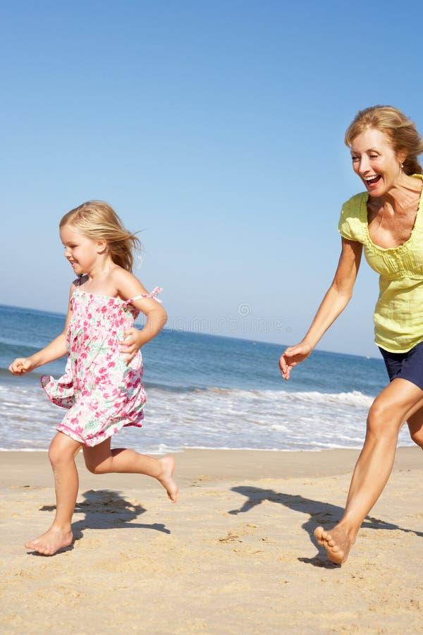 Farmor och sondotter som kör längs strand arkivfoton