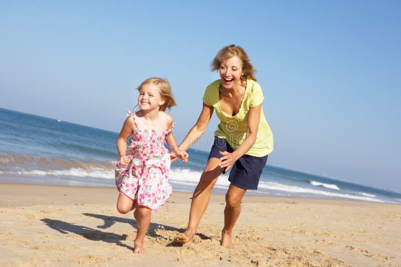 Farmor och sondotter som kör längs strand royaltyfri foto