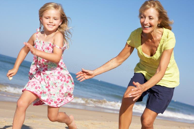 Farmor och sondotter som kör längs strand royaltyfria bilder